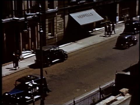 cars driving down street with people walking on sidewalk / london england united kingdom - einige gegenstände mittelgroße ansammlung stock-videos und b-roll-filmmaterial