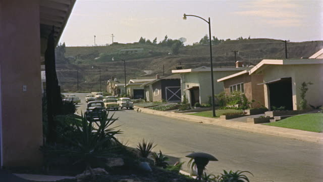 1955 ws cars driving down suburban street / los angeles, united states - 1950 stock-videos und b-roll-filmmaterial