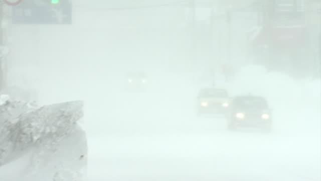 cars driving in blizzard, hokkaido, japan - 通路点の映像素材/bロール