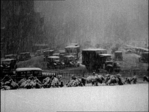 cars driving in blizzard on city street / policeman with umbrella directing traffic. blizzard hits washington dc on february 05, 1934 in washington,... - 1934 stock videos & royalty-free footage