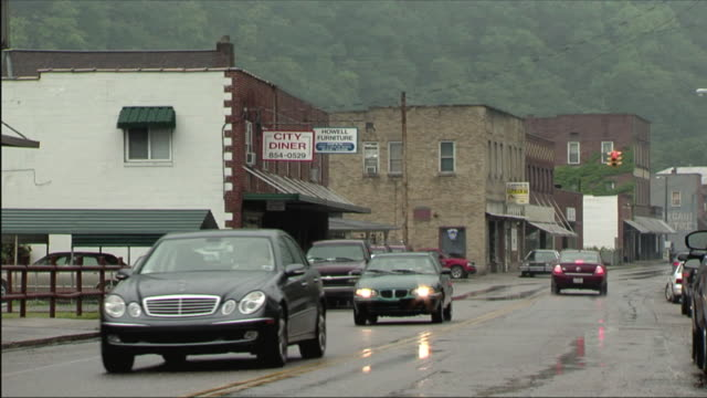 stockvideo's en b-roll-footage met ms cars driving in rain along main street of small appalachian town / bob white, west virginia - virginia amerikaanse staat