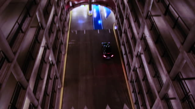 stockvideo's en b-roll-footage met cars driving inside a huge concrete parking withs colors and nice round shapes. - parkeren