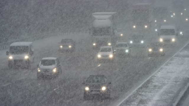 ld cars driving on a highway in a heavy snow storm - snowing stock videos & royalty-free footage