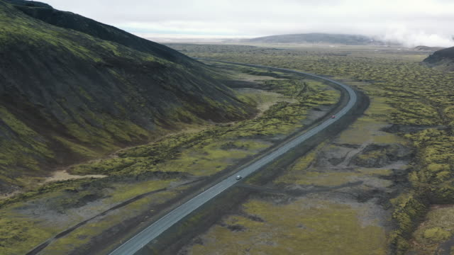 cars driving on a road crossing volcanic landscape seen from an aerial point of view, iceland - rock strata stock videos & royalty-free footage