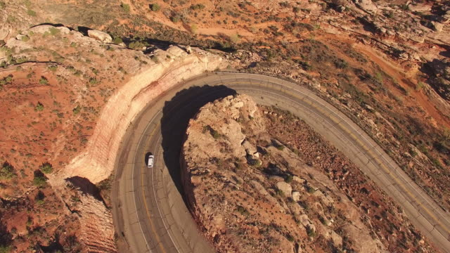 AERIAL Cars driving on a winding road in desert