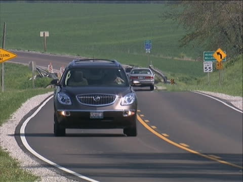 ls cars driving on a winding road in the middle of grass fields good generic stock shot of the country - winding road stock videos & royalty-free footage