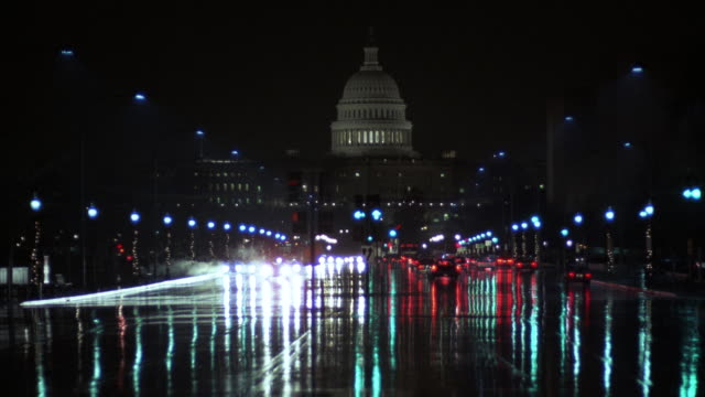 MS Cars driving on busy street with lighted dome of the Capitol building behind / Washington DC, United States