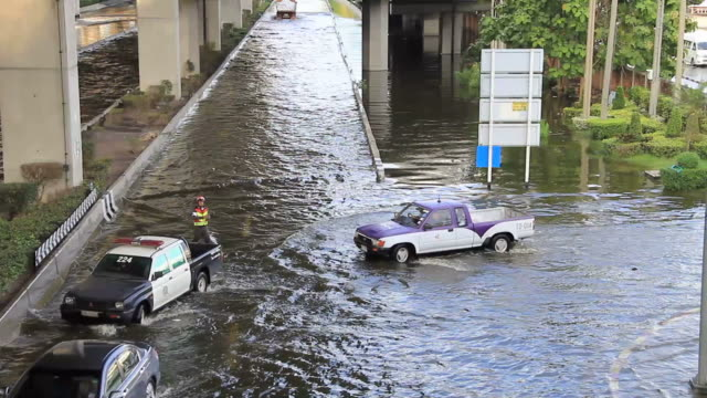 Cars driving on flood road.