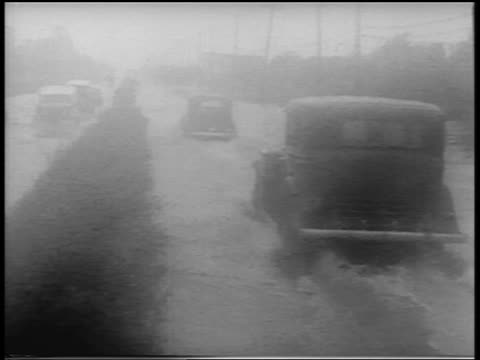 B/W 1938 cars driving on flooded street in rain during hurricane / Northeast US / newsreel
