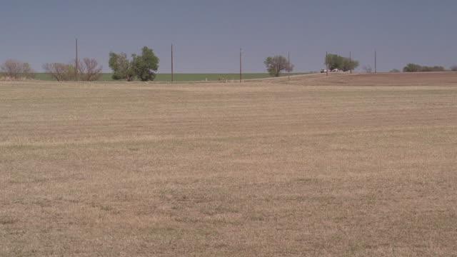 WS Cars driving on road running alongside farm field / Kaufman, Texas, United States