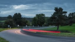 Cars driving on the asphalt curvy road through green fields and forests. Time lapse zooming out.