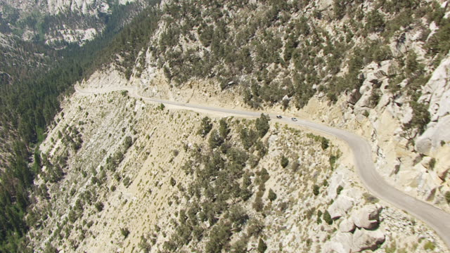 ws tu td aerial pov cars driving on whitney portal road of sierra nevada with mountain in background / california, united states  - californian sierra nevada stock videos & royalty-free footage
