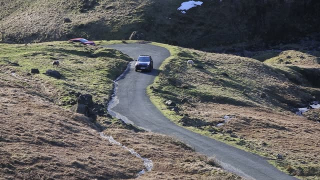Cars driving over Wrynose Pass in the Lake District, UK.