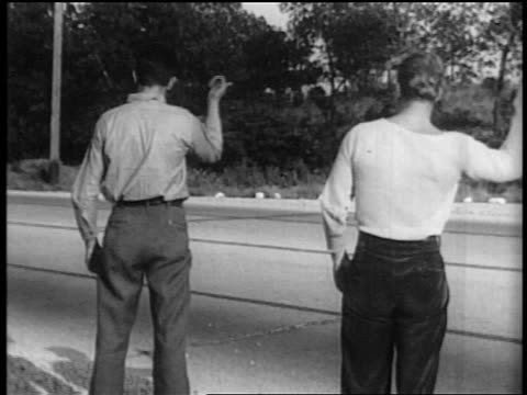cars driving past 2 men with thumbs raised hitchhiking alongside highway - 1935 stock videos & royalty-free footage