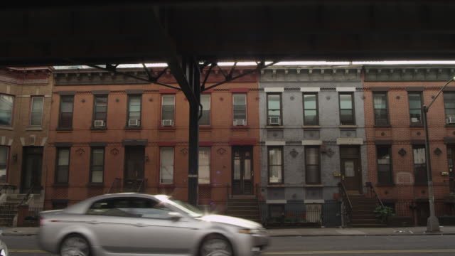 stockvideo's en b-roll-footage met ms cars driving past a set of row houses. - stadswoning
