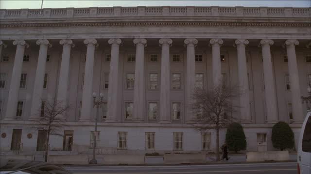 la cars driving past columns on side of u.s. treasury building / washington, d.c., united states - 新古典派点の映像素材/bロール