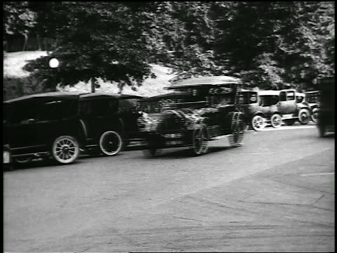 b/w 1920 cars driving past diagonally parked cars / newsreel - 1920 stock videos & royalty-free footage