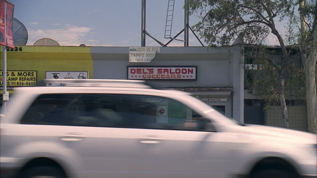stockvideo's en b-roll-footage met ws cars driving past entrance to del's saloon on santa monica blvd / los angeles, california, usa - bar gebouw