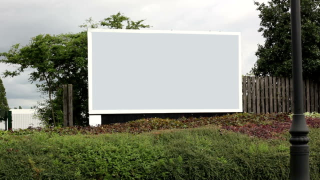 cars driving past grey advertising billboard - billboard stock videos and b-roll footage