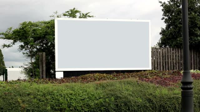 Cars driving past Grey Advertising Billboard