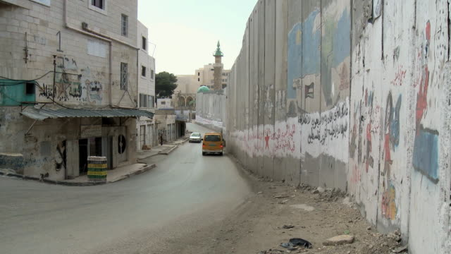 ws pan cars driving past israeli west bank wall / jerusalem, israel - auseinander stock-videos und b-roll-filmmaterial
