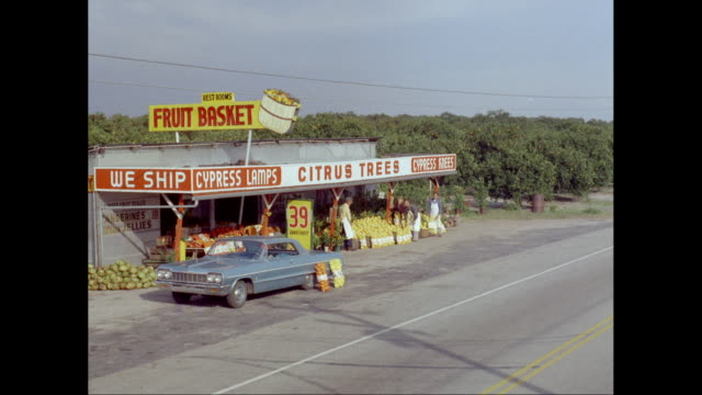ws cars driving past roadside fruit stand / united states - straßenrand stock-videos und b-roll-filmmaterial