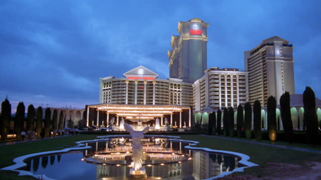 la ws cars driving past statue and pond outside entrance to caesar's palace hotel and casino / las vegas, nevada, usa - caesars palace las vegas stock videos & royalty-free footage