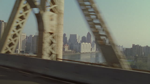 vídeos de stock e filmes b-roll de cars driving past the steel beams of the manhattan bridge overlooking the new york city skyline. - ponte de manhattan