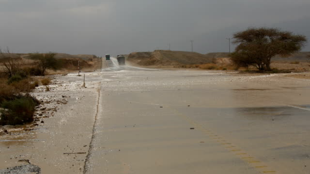 Cars driving through flooded desert road after Flash flood / Arava Valley& Negev Desert, Israel