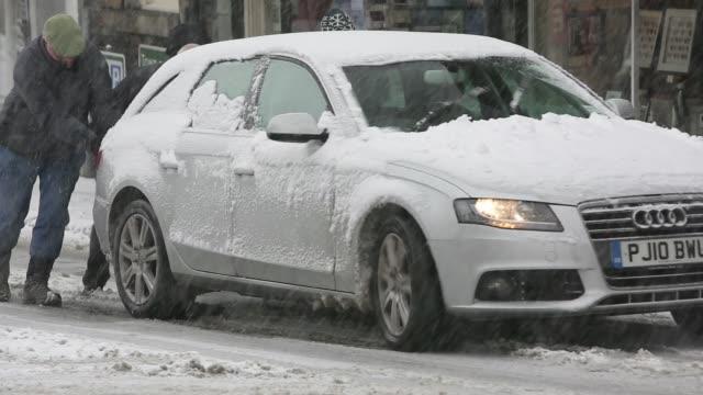 cars driving through heavy snow in ambleside, lake district, uk. - pushing点の映像素材/bロール