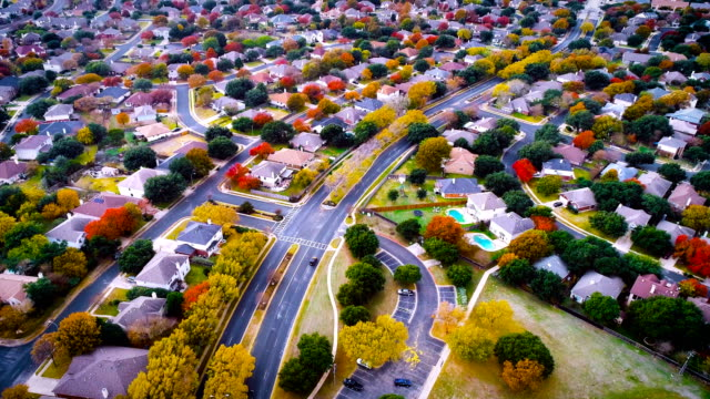 cars driving to and from home in suburb neighborhood aeiral drone view high above expanding housing development - modern rock stock videos & royalty-free footage