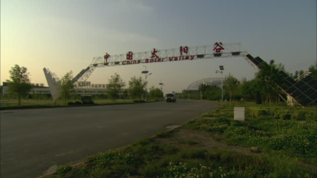 WS Cars driving under pedestrian walkway reading China Solar Valley, Dezhou, Shandong, China