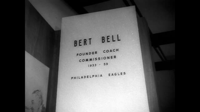 cars driving up to football hall of fame / cu of sign in front of building / inside the exhibition area / cu exhibit for bert bell / george halas... - hall of fame stock videos and b-roll footage