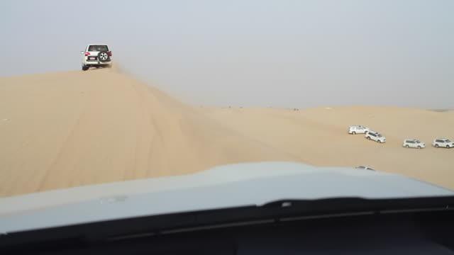 cars dune bashing on a desert safari, abu dhabi - dirt track stock videos & royalty-free footage