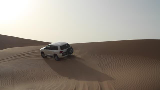 cars dune bashing on a desert safari, abu dhabi - sand dune stock videos & royalty-free footage