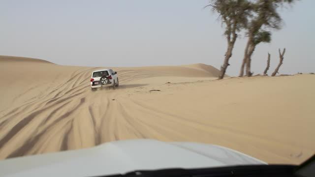 Cars dune bashing on a desert safari, Abu Dhabi