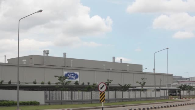 ws cars enter the ford motor co factory through the main gate ws pan rl to ford motor co factory's main gate ws pan rl as a truck drives past the... - ford marca di veicoli video stock e b–roll