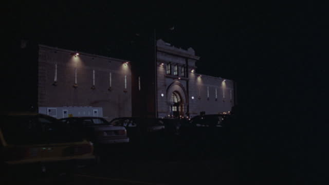 cars fill a parking lot outside of a prison. - prison building stock videos & royalty-free footage