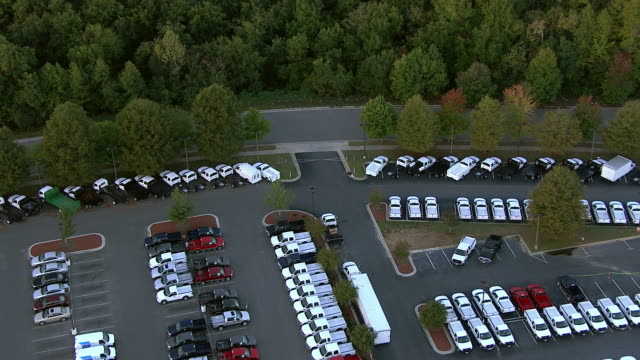 vídeos de stock e filmes b-roll de cars fill the parking lots at the young ford dealership. - stand de carros