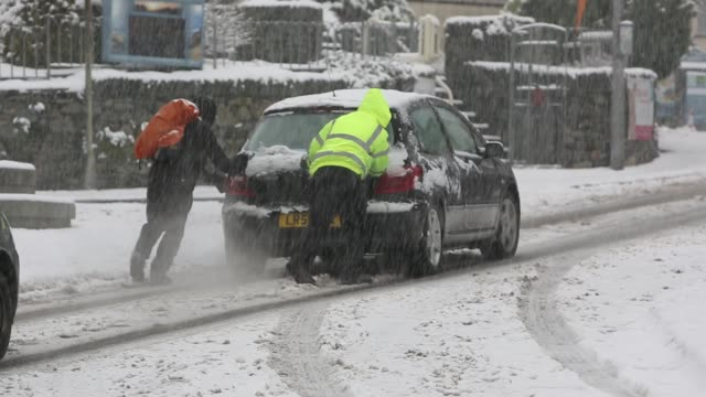 cars getting stuck and needing pushing driving through snow in ambleside in the lake district uk - snowing stock videos & royalty-free footage