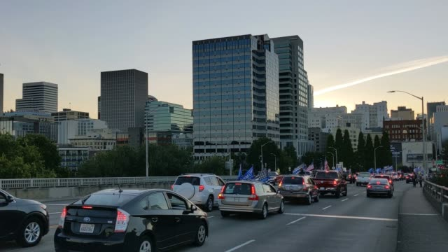 cars go by with flags attached waving as pro-trump supporters drive into downtown during a rally in support of the president on august 29, 2020 in... - portland oregon stock videos & royalty-free footage