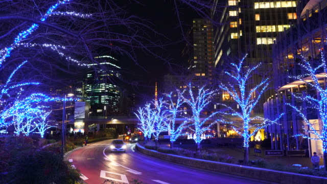 cars go through among the illuminated trees line street along high-rise buildings at tokyo midtown roppongi tokyo japan december 21 2017. over 500,000 led lights illuminate the street and surround the area for christmas illumination event. - tokyo midtown stock videos & royalty-free footage