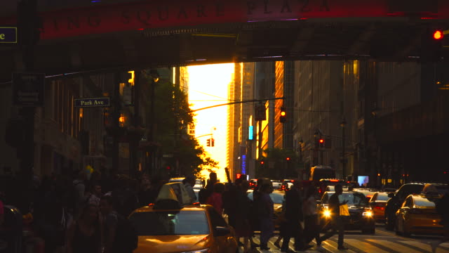 cars go through under the pershing square bridge and people cross the 42nd street while sun is setting for manhattanhenge new york u.s.a on 30 may 2018. the sky, buildings, street and people glows for the sunset. - taxi stock videos & royalty-free footage