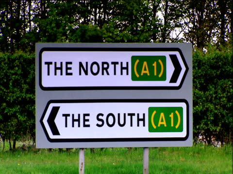 Cars heading north past road sign showing directions to both north and south