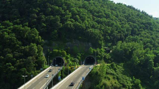 auto che si dirigono sul ponte autostradale in galleria vicino a castellfollit de la roca - colpo di drone - roca video stock e b–roll