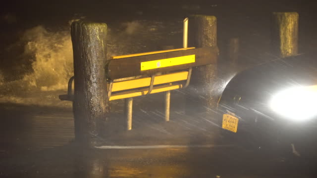 A car's headlights illuminate heavy windswept rain as a powerful night time nor'easter batters a marina on Long Island with very rough surf