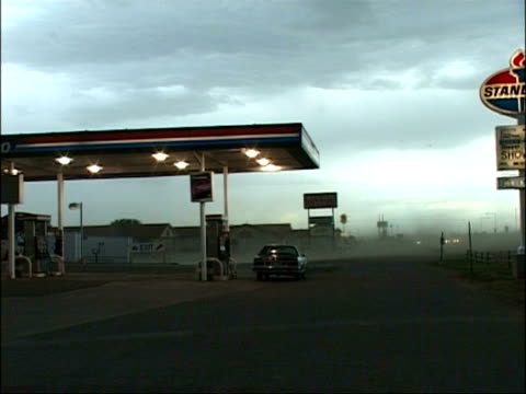 MS Cars in petrol station forecourt with dust storm blowing left to right across frame, 1 car moves off, USA