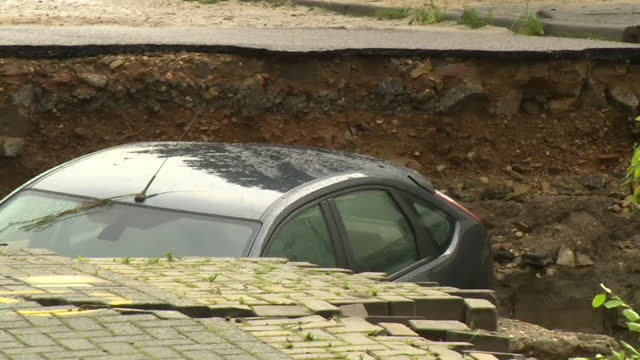 """cars in sink hole after flooding devastated valkenburg, in the limburg province of netherlands - """"bbc news"""" stock videos & royalty-free footage"""