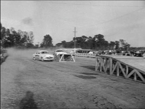 b/w 1948 pan 2 cars in stunt show / one jumping over other + landing safely documentary - stunt video stock e b–roll