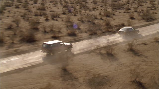cars leave a trail of dust as they drive though the desert. - セージブラッシュ点の映像素材/bロール